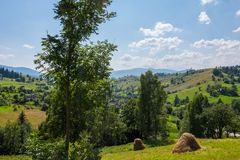 Hay stacks on the slope of the green mountain against the backdrop of a small rural village with pretty houses. For your design stock photos