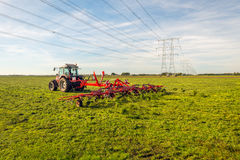 Free Hay Tedding In A Dutch Landscape With High Voltage Pylons And Li Stock Images - 80323234
