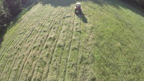 retro tractor cut grass from summer end meadow, aerial view stock footage