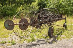 Hay Turner arrugginito anziano Vecchia attrezzatura agricola su fieno Immagini Stock Libere da Diritti