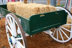 Hay Wagon 5758. A green wagon with white wheels holds bales of hay.  Hay covers the ground Royalty Free Stock Photo