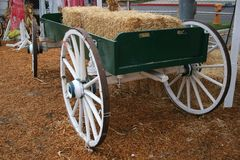 Hay Wagon 5759. A green wagon with white wheels holds bales of hay.  Hay covers the ground Royalty Free Stock Images