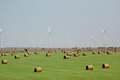 Hay and wind farm. Hay bales and green grass in the foreground and Kansas wind farm in the distance Royalty Free Stock Images