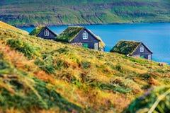 Haymaker on Bour village. Splendid morning view of  typical turf-top houses on Vagar island, Faroe, Kingdom of Denmark, Europe. Tr