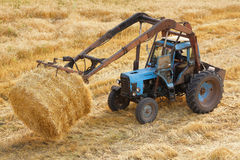 Haymaking. By tractor on hayfield royalty free stock images