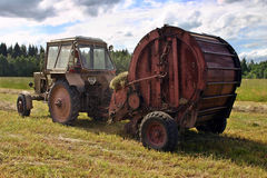 Haymaking time, round baling hay and farming tractor in farmland Stock Photo