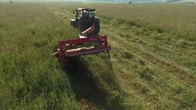 Haymaking. A tractor with a trailer-mower mowing grass. Produced hay making stock video footage