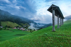 Hayrack on hilltop and Sorica village in Slovenia.  royalty free stock images