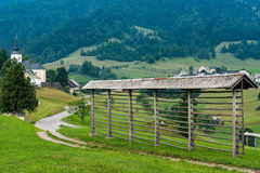 Hayrack on hilltop and Sorica village in Slovenia.  stock photos
