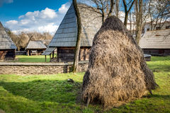 Hayrick in a Romanian village. Rural image of a romanian village in eastern europe, with a hayrick in the foreground and traditional farm houses in the Stock Photo