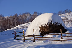 Hayrick at winter. Snow-covered hayrick with a wooden fence Stock Photos