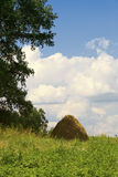Haystack against a green grass and the blue sky Stock Photo