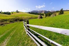 Haystack behind the wooden fence on a grassy hill. Beautiful Carpathian countryside in springtime. mountain ridge with snowy tops in the distance Stock Photos