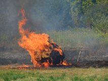 Haystack in fire in a hot summer day. Vegetation fire emitting smoke in a hot summer day royalty free stock photography