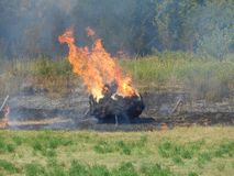 Haystack in fire in a hot summer day. Vegetation fire emitting smoke Stock Photography