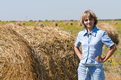 Haystack and girl. On the meadow in sunny day Stock Images