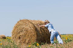 Haystack and girl. On the meadow in sunny day Royalty Free Stock Photography