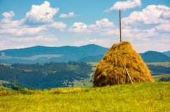 Haystack on a grassy field on top of a hill. Beautiful mountainous countryside scenery in summer Royalty Free Stock Image