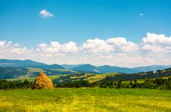 Haystack on a grassy field on top of a hill. Beautiful mountainous countryside scenery in summer Stock Images