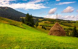 Haystack on a grassy meadow in mountains. Beautiful landscape under the azure sky with gorgeous cloudscape Stock Image