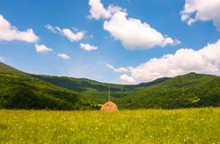 Haystack on a grassy pasture in mountains. Beautiful summer scenery on a fine weather day Stock Image
