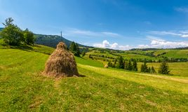 Haystack on a grassy rural field in mountains. Beautiful countrye landscape with forested hills on a fine summer day Royalty Free Stock Photo