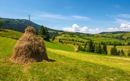 Haystack on a grassy rural field in mountains. Beautiful countrye landscape with forested hills on a fine summer day Stock Photography