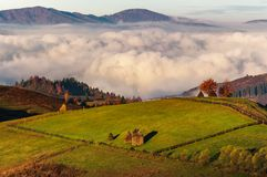Haystack on hillside above the clouds at sunrise. Gorgeous rural landscape in high mountains Royalty Free Stock Image
