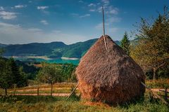 Haystack with the lake in the background. Landscape view of an orange haystack with contrasting blue lake and sky in the distance behind it royalty free stock image