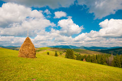Haystack on mountain meadow with blue cloudy sky. Ukraine, Europe Royalty Free Stock Photos