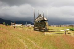 Haystack on mountain meadow with stormy sky royalty free stock photography
