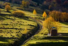Haystack near the path on hillside in autumn. Haystack behind the fence near the path on hillside in autumn. beautiful countryside scenery with yellow trees Royalty Free Stock Image