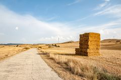 A haystack next to the road in the countryside. A beautiful haystack is located next to the rural road in Spain, Navarra. Soon the sunset and sunlight painted stock photography