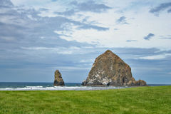 Haystack rock on cannon beach. Scenic view of Haystack Rock on cannon beach in Oregon with cloudscape in background; U.S.A Stock Photography
