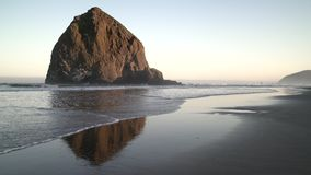 Haystack Rock, Cannon Beach Dawn 4K. UHD. Sunrise at Haystack Rock in Cannon Beach, Oregon as the surf washes up onto the beach. United States stock footage