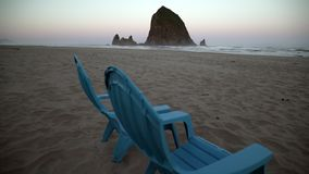Haystack rock and deck chairs, Cannon beach dawn 4K. UHD. Dawn at haystack rock in Cannon beach. Deck chairs to watch the surf washes up onto the beach. United stock video footage