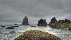 Haystack rock formations on the Oregon Coast. Haystack rock formations on the Oregon Coast, just south of the famous Haystack.  Cloudy skies and mussel covered Stock Photo
