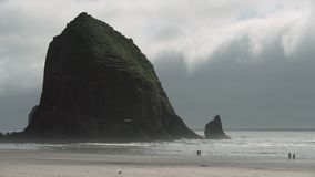 Haystack Rock Mist, Cannon Beach 4K. UHD. Mist at Haystack Rock in Cannon Beach, Oregon as the surf washes up onto the beach. United States. 4K UHD stock footage