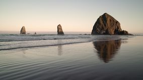 Haystack Rock and the Needles, Cannon Beach 4K. UHD. Sunrise at Haystack Rock and the Needles in Cannon Beach, Oregon as the surf washes up onto the beach stock footage