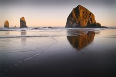 Haystack Rock Sunrise, Cannon Beach, Oregon. Sunrise at Haystack Rock in Cannon Beach, Oregon as the surf washes up onto the beach. United States royalty free stock photo