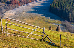 Haystack on the rural field on hillside. Haystack behind the fence on the rural field on hillside. frosty grass in forest shade at sunrise in autumn Stock Photos
