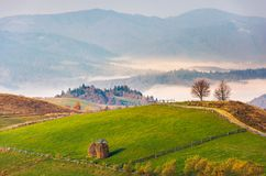 Haystack on rural fields in foggy mountainous area. Beautiful countryside landscape in autumn. forested hill and valley in fog behind the nearest knoll on a stock photography