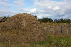 Haystack standing near wooden fence in the village. Autumn harvest. Ukraine, Sumy region. Stock Photo