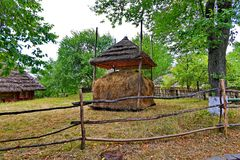 A haystack under a canopy covered with a thatched roof in the courtyard of a rural manor is fenced with a hedge with