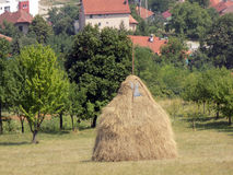 Haystack in village. Beautiful haystack located near houses stock photo