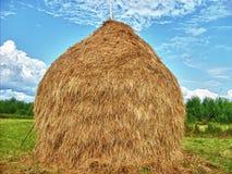 Haystack y aldea del cielo azul Fotos de archivo libres de regalías