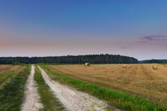 Haystacks by the country road. August countryside landscape. Masuria, Poland Royalty Free Stock Image