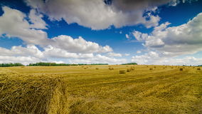 Haystacks On The Field Under The Clouds Time Lapse 4K. Yellow haystacks on the field under the clouds time lapse 4k stock video footage