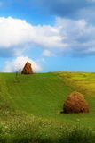 Haystacks on Green field. Sustainable living in eco friendly environment Royalty Free Stock Images