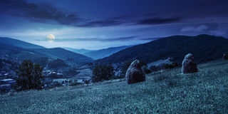 Haystacks on hillside near the village at night Royalty Free Stock Image